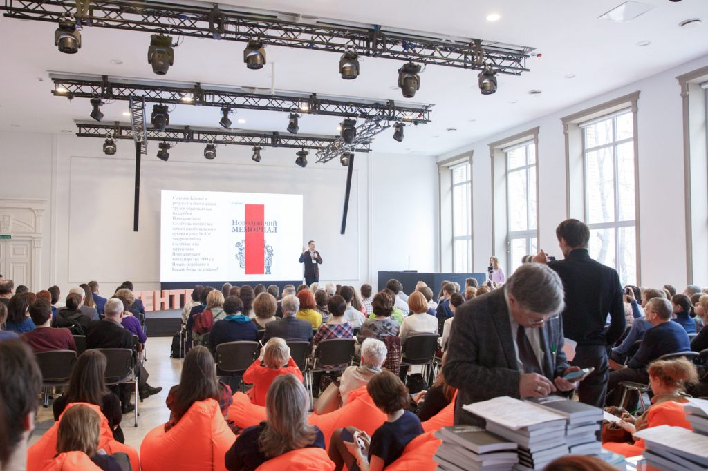 Люди сидят на генеалогическом форуме ГЕНТЕХ 2020 и слушают лекцию